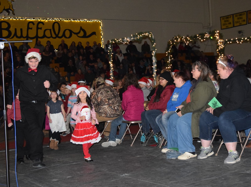 Caliche Elementary students, all wearing Santa hats, parade out underneath Christmas arches, while the school band plays, at the conclusion of the school's Christmas Celebration Tuesday, Dec. 5, 2017.