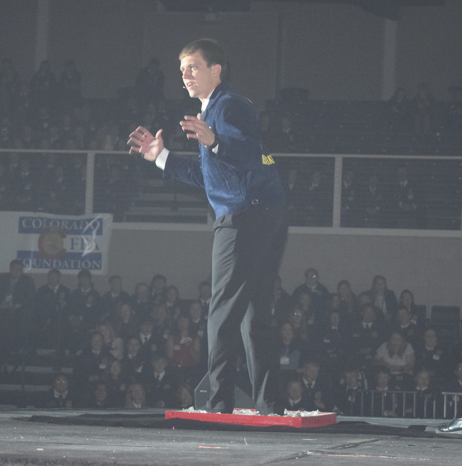 """Colorado FFA State Sentinel Nick Vollmer, of Merino, demostrates the theme of session 2, """"Intensify Your Experience,"""" as he walks across broken glass during the Colorado FFA State Convention Wednesday, June 8, 2016."""