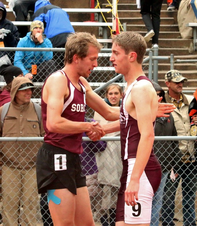 . Zach Karg (right) of Merino High School shakes hands with a competitor after the 1,600 meter run in Lakewood over the weekend. (photo by Melanie Kindvall)