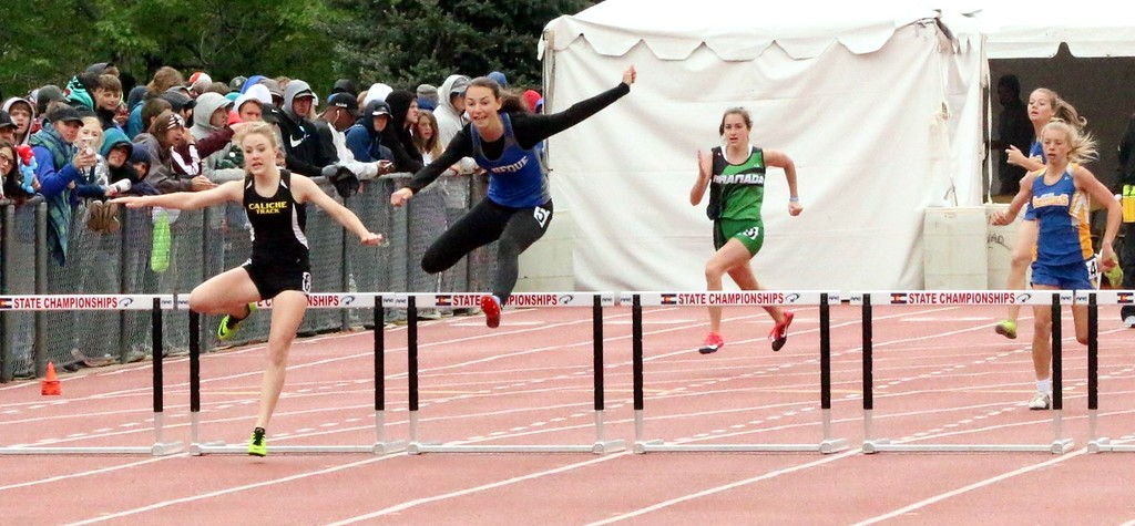. Kaitlyn Houghton (left) clears a hurdle before the competition on Saturday in Lakewood. Houghton finished second in the 300 meter hurdles and fourth in the 100 meter hurdles. (photo by Melanie Kindvall)