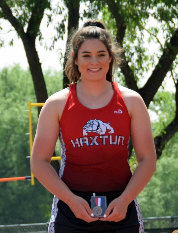 . McKenna Andersen of Haxtun High School stands on the podium after taking fourth place in the shot put at the state meet. (photo by Kyle Inman)