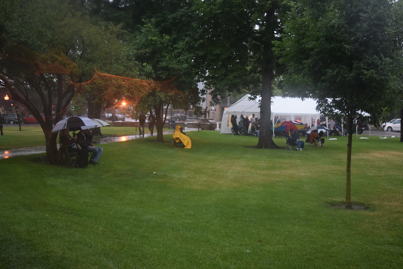 Concertgoers take cover under a tent and umbrellas as they listen to the music of George Gray and the Elvis Experience at Transwest Concerts on the Green...July Jamz Friday, July 1, 2016.