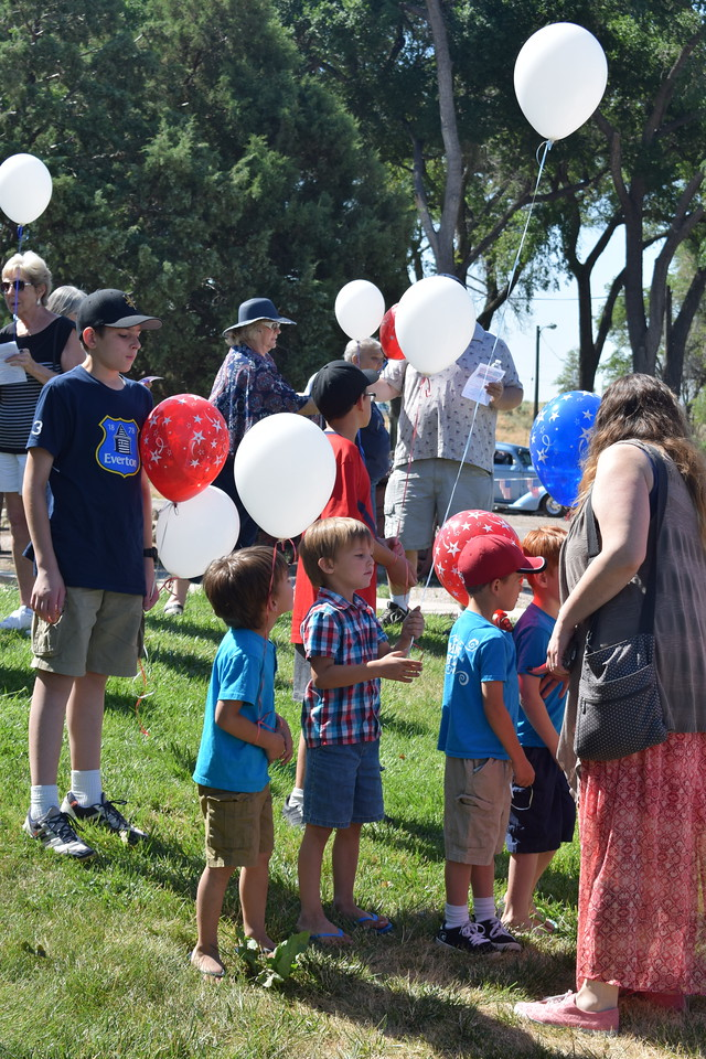 Guests hold balloons as they await the start of the Heritage Festival opening ceremony Tuesday morning, July 4, 2017, at the Overland Trail Museum.