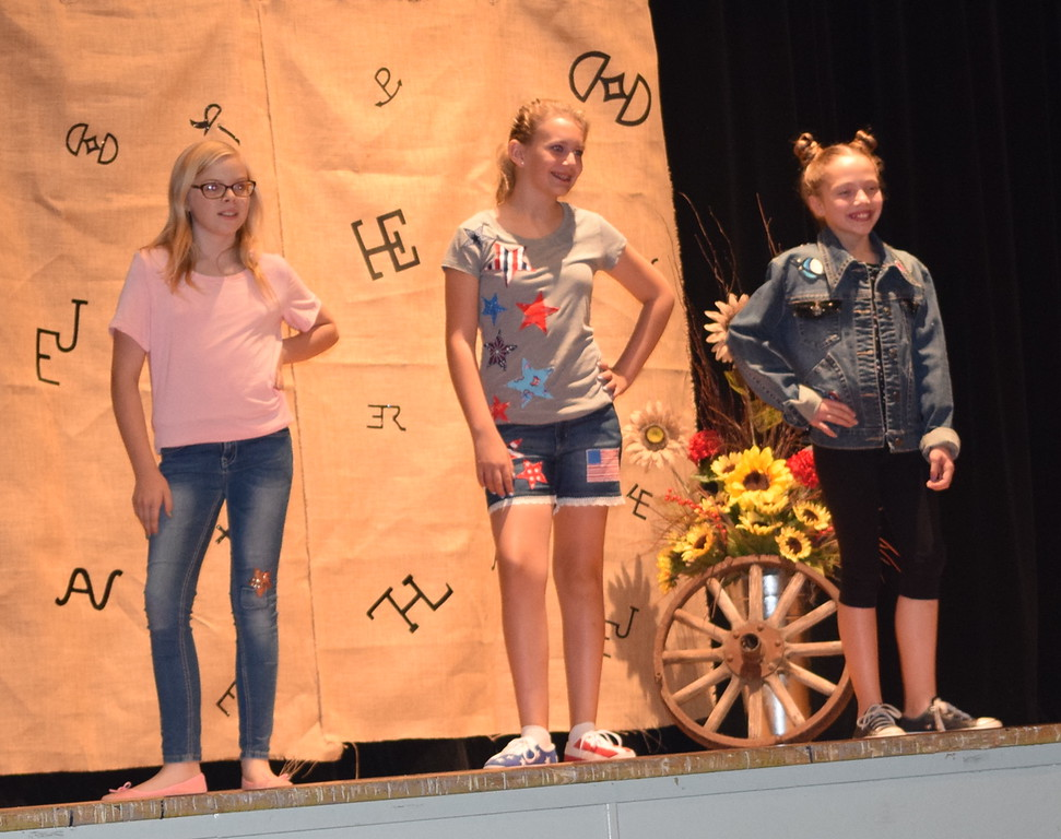 . Contestants in the Intermediate Division of the Logan County Fair 4-H Fashion Revue Friday, Aug. 3, 2018, model their outfits. From left; Sadie Fehringer, Ashton Nichols, Reserve Champion, and Ayla Baney, Champion.