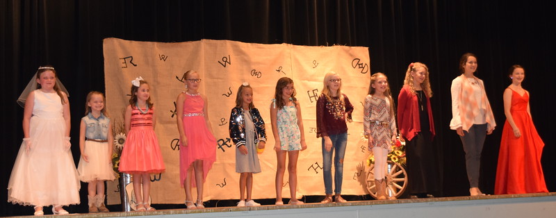 Competitors in the Encore Division of the Logan County Fair 4-H Fashion Revue Friday, Aug. 3, 2018, model their outfits. From left; Ailey Paxton, Piper Withers, Taylor Tribbett, Natalie Adels, Livie Ziegler, Alexis Gentry, Sadie Fehringer, Ayla Baney, Ashton Nichols, Rachael Northup and Aly Young.