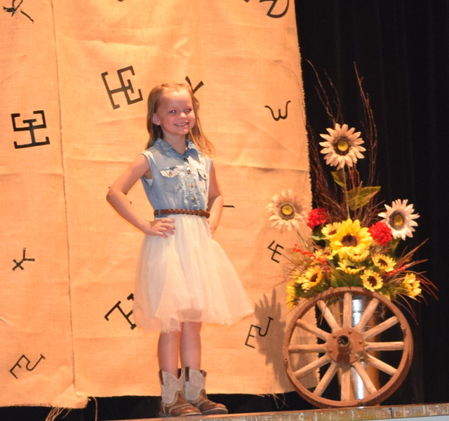 Piper Withers models her dress and cowgirl boots in the Encore Division of the Logan County Fair 4-H Fashion Revue Friday, Aug. 3, 2018.