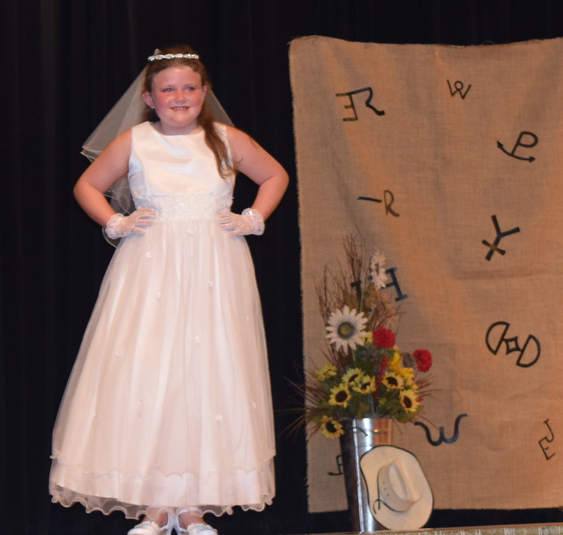 . Ailey Paxton models her communion dress in the Encore Division of the Logan County Fair 4-H Fashion Revue Friday, Aug. 3, 2018.