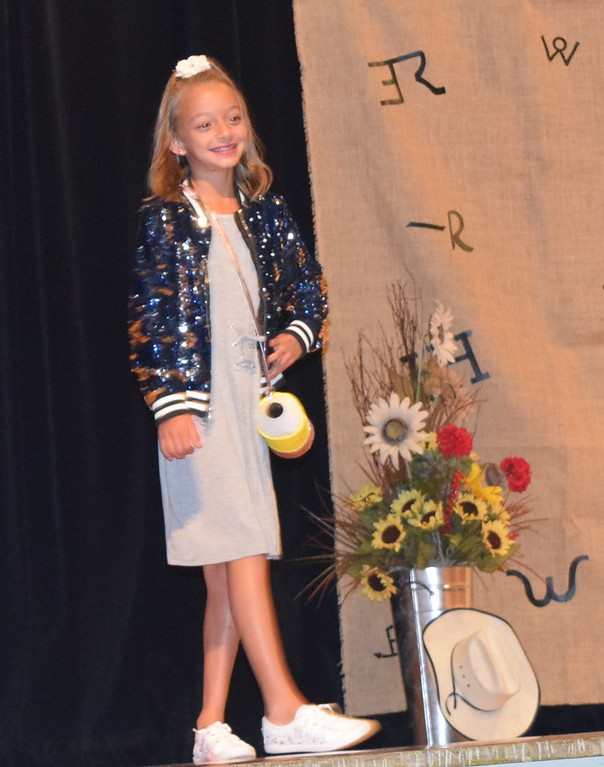 . Livie Ziegler models her dress, jacket and purse in the Encore Division of the Logan County Fair 4-H Fashion Revue Friday, Aug. 3, 2018.