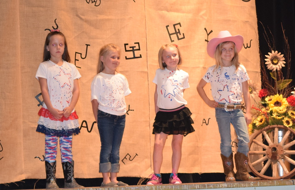 . Cloverbuds Amanda Fehringer, Danni Williams, Laramie Sexton and Rhylee Foos model the shirts they made during the Logan County Fair 4-H Fashion Revue Friday, Aug. 3, 2018. Not pictured is Gia Bella San Miguel.