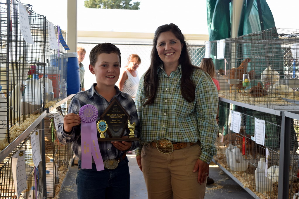 . Jake Gillham, Reserve Champion Poultry Production, poses for a photo with judge Kyla Foltz following the Logan County Fair Junior Poultry Show Thursday, Aug. 9, 2018.