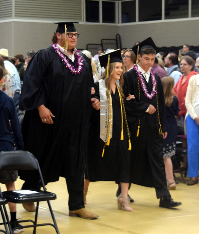 . Clayton Funkhouser, Cristen Houghton and Tristan Lambrecht make their way to their seats at Caliche High School\'s Commencement Ceremony Saturday, May 25, 2019.