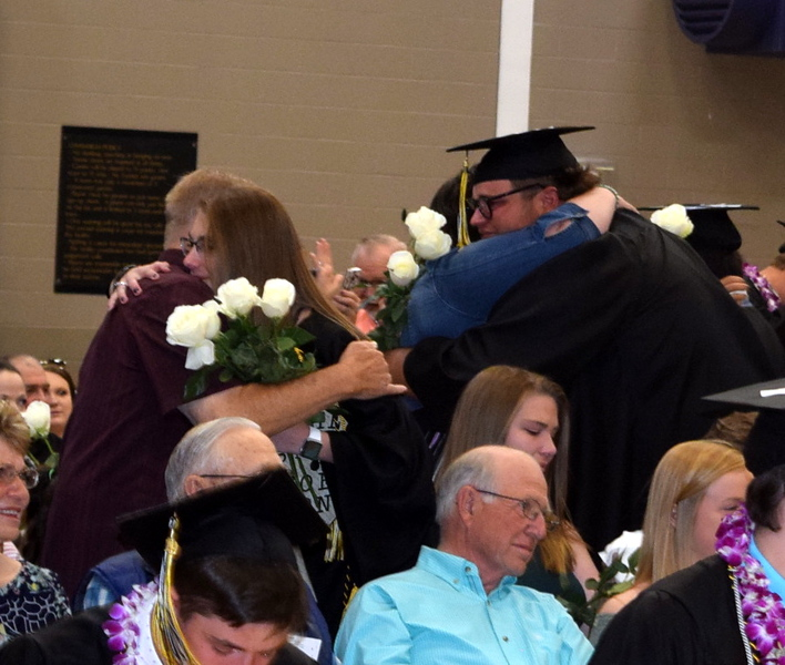 Jenzie Grauberger and Clayton Funkhouser get hugs from lvoed ones as they hand out flowers to family and friends during Caliche High School's Commencement Ceremony Saturday, May 25, 2019.