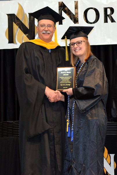 Northeastern Junior College Associated Student Government Secretary Brooke Corliss presents the Joel E. Mack Award to Kevin Stump, math and physics instructor, at NJC's Commencement Ceremony Friday, May 17, 2019.