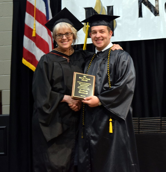 Northeastern Junior College Associated Student Government First Vice President Logan Bivens presents the Joel E. Mack Award to Stephanie Weatherill, English instructor, at NJC's Commencement Ceremony Friday, May 17, 2019.