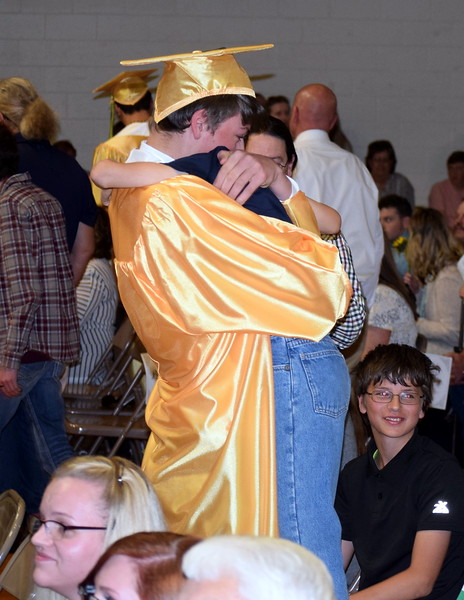 Bryson Long gives a hug to a loved one as graduates hand out flowers to family and friends at Peetz School's Commencement Ceremony Sunday, May 12, 2019.