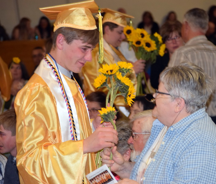 Jakob Kurz presents flowers to a loved one at Peetz School's Commencement Ceremony Sunday, May 12, 2019.