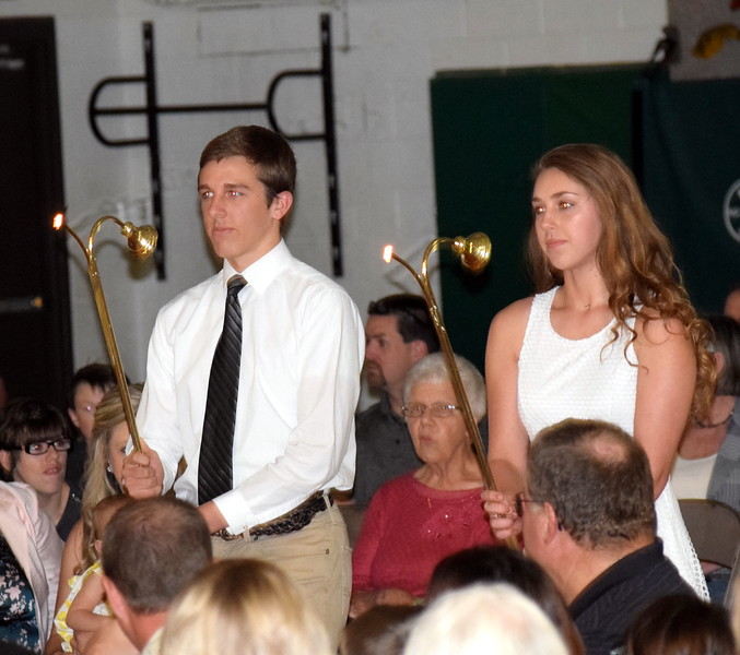 Junior class escorts Caroline Lindahl and Ethan Ramey walk forward to light the candles at the beginning of Peetz School's Commencement Ceremony Sunday, May 12, 2019.