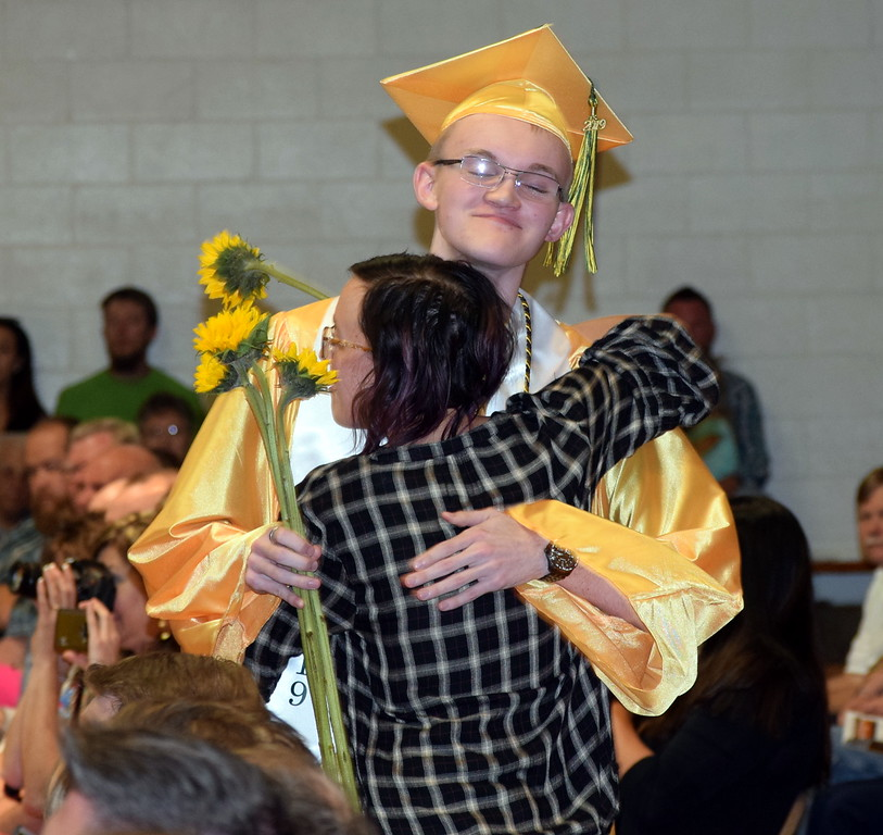 . Dylan Bruner gets a hug from a loved one as graduates present flowers to family and friends at Peetz School\'s Commencement Ceremony Sunday, May 12, 2019.