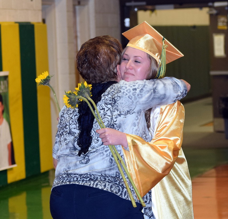 . Sarah Davis gets a hug from a loved one as graduates present flowers to family and friends at Peetz School\'s Commencement Ceremony Sunday, May 12, 2019.