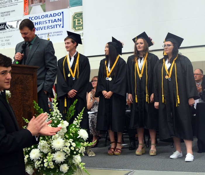 Mark Appelhans, Sterling High School assistant principal, recognizes the four students who maintained a 4.0 or above grade point average while in high school during the commencement ceremony Saturday, May 25, 2019. From left; Greyson Dudley, Jasmine Renteria, Kathleen Masters and Brooke Bohler.