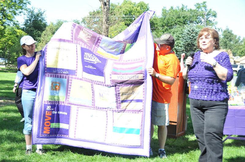Dene Carter, right, talks about the quilt she had made from her Walk to End Alzheimer's T-shirt collection. The quilt was auctioned off last year, then donated back to be auctioned again this year for the Walk to End Alzheimer's.