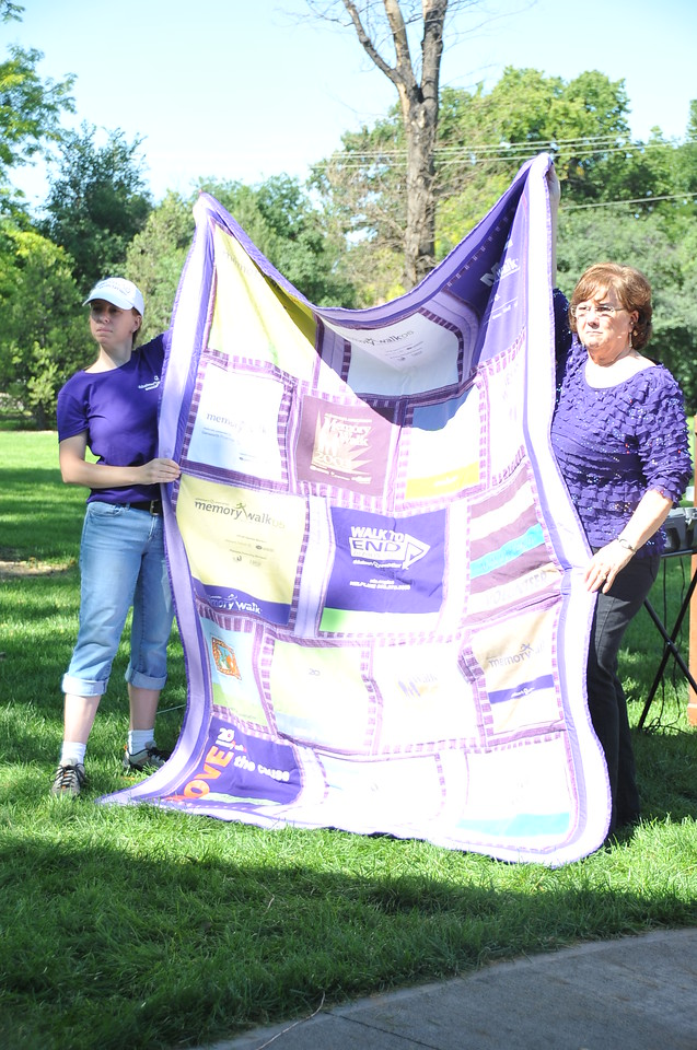 Dene Carter, right, holds the quilt she had made from her Walk to End Alzheimer's T-shirt collection. The quilt was auctioned off last year, then donated back to be auctioned again this year for the Walk to End Alzheimer's and raised $200 Saturday, Aug. 24, 2013, at Columbine Park.