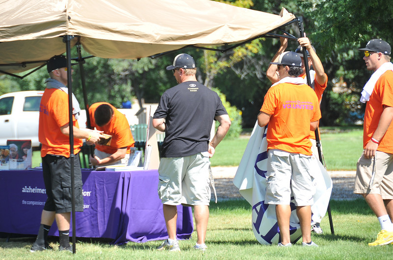 NJC baseball players help tear down booths at the Walk to End Alzheimer's Saturday, Aug. 24, 2013, at Columbine Park.