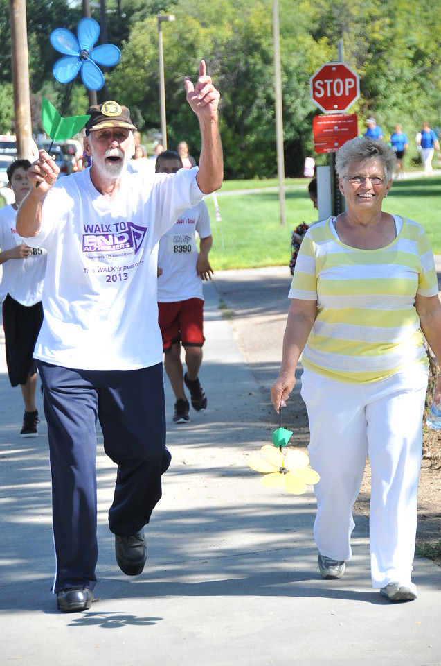 Participants in the Walk to End Alzheimer's carry Promise Garden flowers that show their connection to the fight against Alzheimer's disease on Saturday, Aug. 24, 2013, at Columbine Park.