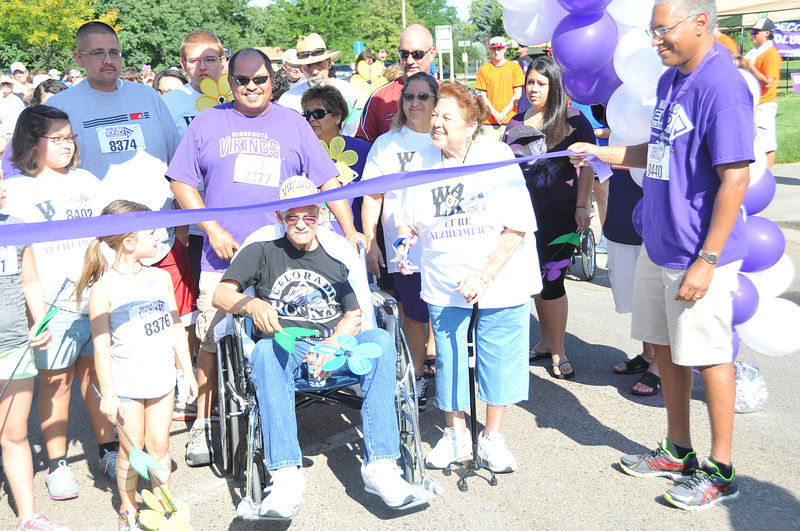 The Efrain Ramos family gathers under the balloon arch to cut the ribbon and start the Walk to End Alzheimer's Saturday, Aug. 24, at Columbine Park.