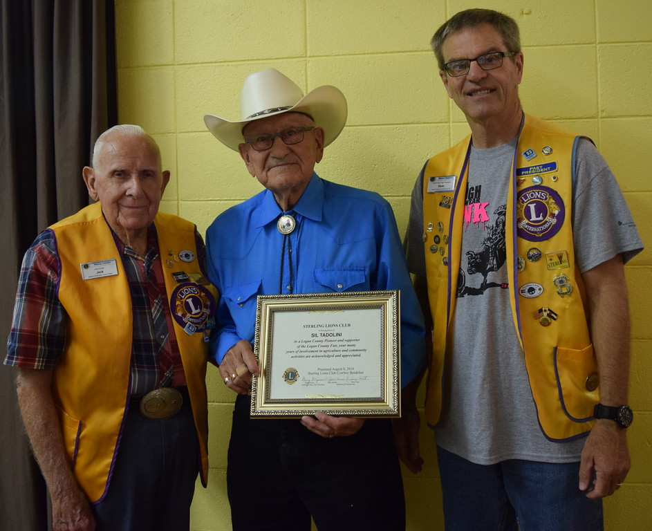 . Sterling Lions Club members Jack Annan, left, and Dave Fast present the Pioneer Award to Sil Tadolini at the club\'s annual Cowboy Breakfast Wednesday, Aug. 8, 2018.