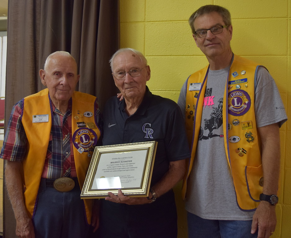 . Sterling Lions Club members Jack Annan, left, and Dave Fast present the Pioneer Award to Maurice John Schaefer at the club\'s annual Cowboy Breakfast Wednesday, Aug. 8, 2018.
