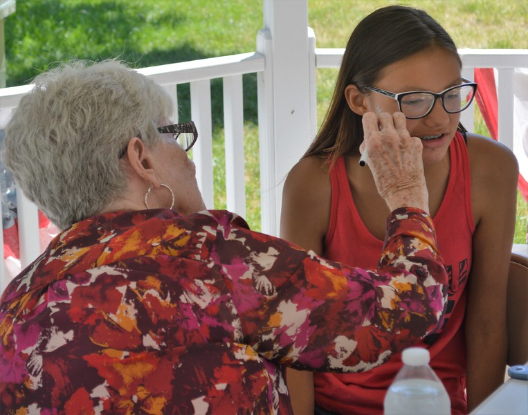 Virginia McConville of Kimball, NE, paints red, white, and blue stars on Violet Tayler's face during the Heritage Festival Monday.
