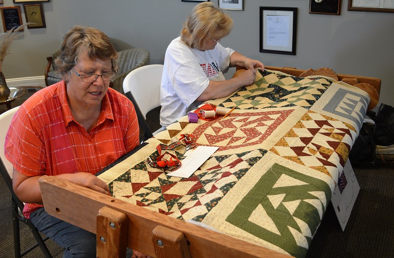 Connie Chambers, left, and Dorothy Schreyer demonstrate old-fashioned quilting during the Heritage Fesitval Monday. Chambers said the two have been working on the same quilt at Heritage Festivals for the past 10 years and hope to have it finished by 2020. (Jeff Rice/Journal-Advocate)