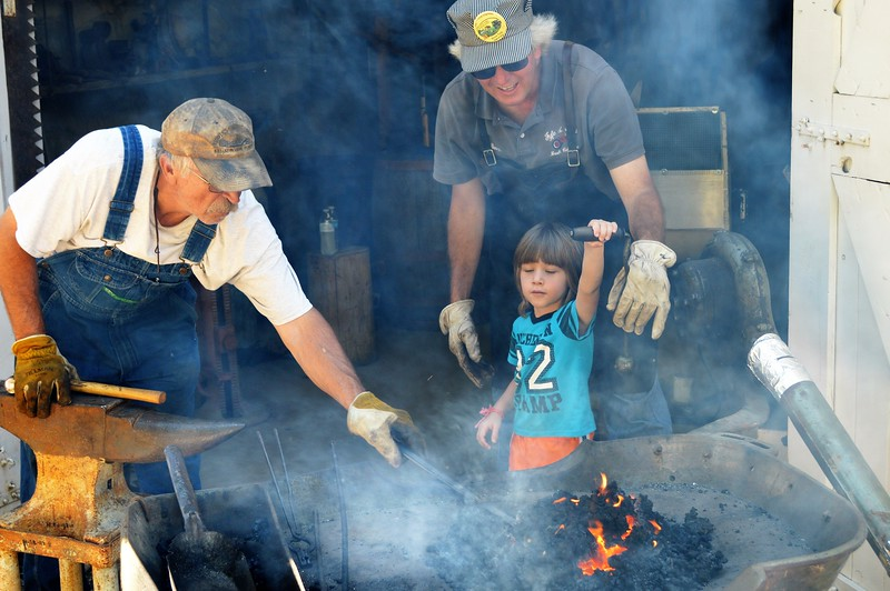 Three-year-old Daylan Michael Baker of Sterling helps Bruce Fyfe of Brush with the forge blower while Dave Ward of Sterling heats iron to make an implement. (Jeff Rice/Journal-Advocate)