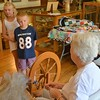 """Carlee Hicks of Sterling and her brother, Alex, watch Ruth Hunter spin yarn from a sheep's wool called """"cotswold."""" Hunter said she's been spining for about 30 years. (Jeff Rice/Journal-Advocate)"""