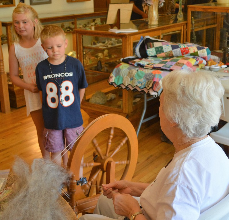 "Carlee Hicks of Sterling and her brother, Alex, watch Ruth Hunter spin yarn from a sheep's wool called ""cotswold."" Hunter said she's been spining for about 30 years. (Jeff Rice/Journal-Advocate)"