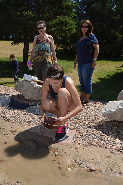 Lauren Rice looks for treasure in the Overland Trail Museum's gold panning creek Monday, July 4, 2016, during the Heritage Festival. (Sara Waite/Journal-Advocate)