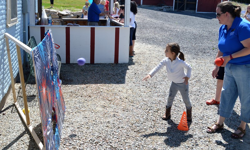 Abby Betley, 5, of Fleming, tries her luck at a ball toss game, coached by Overland Trail Museum staffer Rusty Willson. (Jeff Rice/Journal-Advocate)