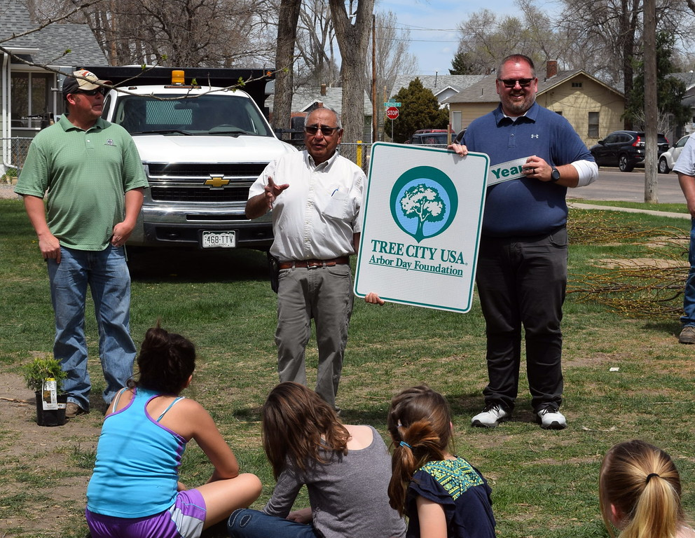 . Sterling Mayor Dan Torres, left, and Parks, Library and Recreation Director Wade Gandee accept a flag from the Colorado State Forest Service marking Sterling\'s 31st year as a Tree City USA during an Arbor Day celebration Friday, April 26, 2019.