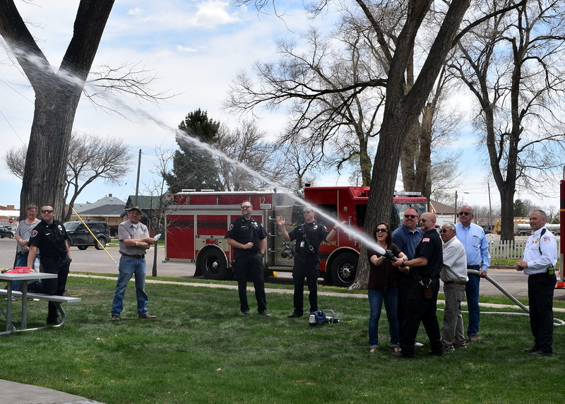 Sterling Firefighter Jason Bostron helps Sterling Mayor Dan Torres, City Manager Don Saling, Parks, Library and Recreation Director Wade Gandee and Sterling City Council member Janice Rice perform a wet down ceremony for the new fire department-themed playround at Monahan Park Friday, April 26, 2019.