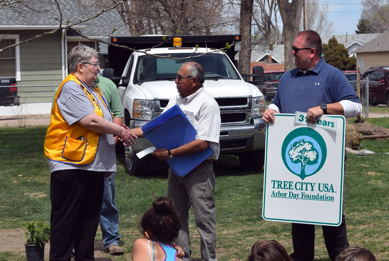 Sterling Lions Club President Loni Stumpff presents a donation in honor of late Lion Dorothy Graber to Sterling Mayor Dan Torres and Parks, Library and Recreation Director Wade Gandee at an Arbor Day celebration at Monahan Park Friday, April 26, 2019. The donation was used to purchase five new trees that were planted in the park.