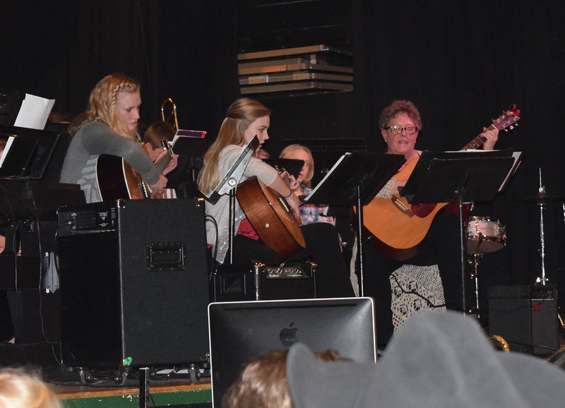 """High school guitar students Hannah Blom and Morgan Cockroft join director Jeri Anderson in a performance of """"Greensleeves,"""" during Fleming School's 5-12th grade Christmas concert Tuesday, Dec. 13, 2016."""