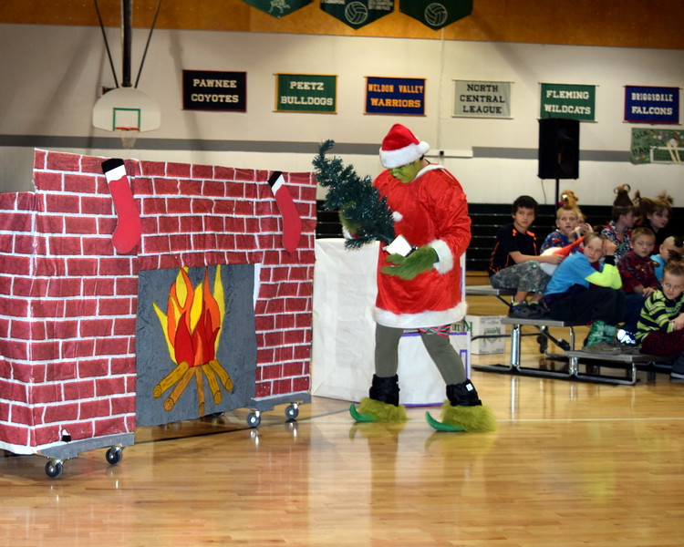 "The Grinch (Darian Wilkening) prepares to stuff a Christmas tree up a chimney as he steals Christmas from the people of Whoville during Fleming Elementary's Reader's Theatre presentation of ""How the Grinch Stole Christmas"" Thursday, Dec. 15, 2016."
