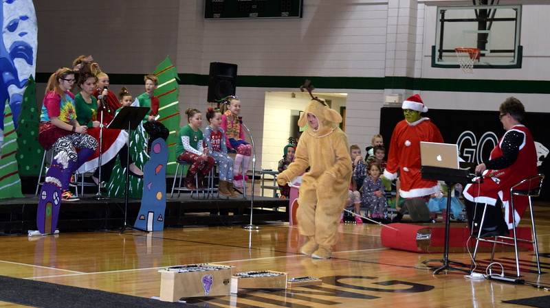 "The Grinch (Darian Wilkening), disguised as Santa Claus, rides in his sleigh, led by his dog, Max (Bailey Chintala), to the town of Whoville to steal Christmas during Fleming Elementary's Reader's Theatre presentation of ""How the Grinch Stole Christmas"" Thursday, Dec. 15, 2016."