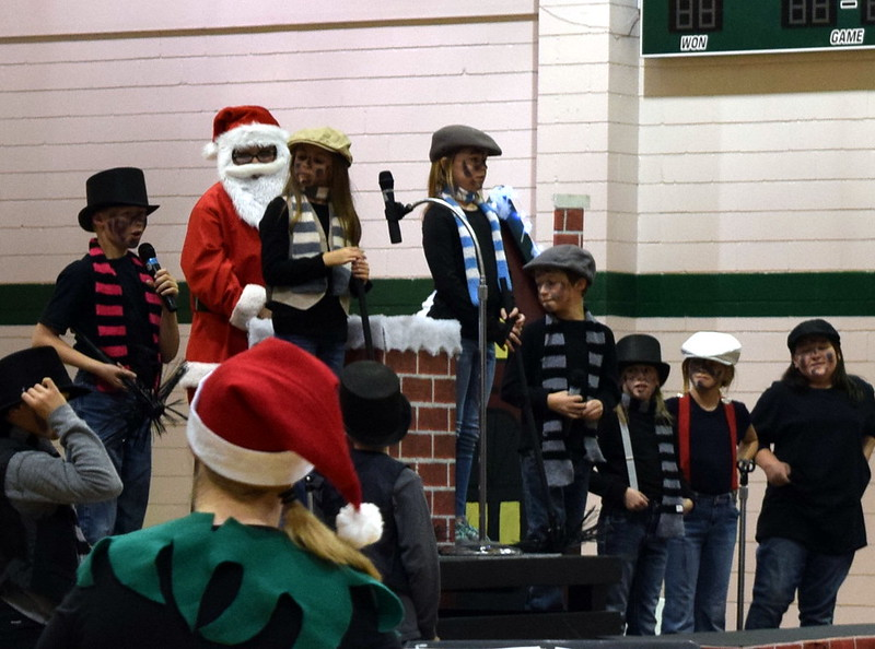 "Chimney sweeps try to help clear a chimney so Santa can make his way down during Fleming Elementary's production of ""Once on a Housetop"" Monday, Dec. 11, 2017."