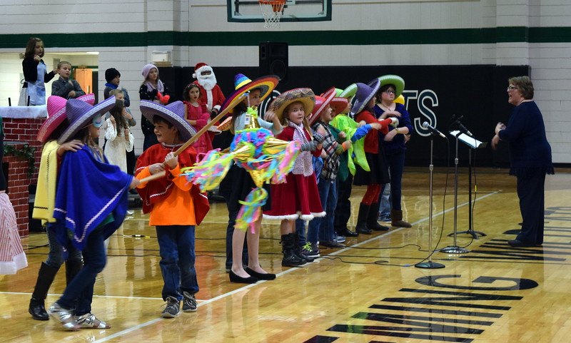"Third grade students try to break a pinata as their classmates sing ""Break the Pinata"" during the Fleming Elementary's production of ""Once on a Housetop"" Monday, Dec. 11, 2017. In this scene, students were celebrating Las Posadas, a Mexican American celebration."