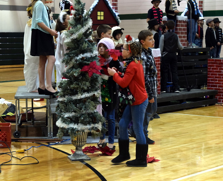 "Students deocrate a Christmas tree as Fleming Elementary second through fourth graders sing ""Holly and Ivy and Evergreen"" during the school's production of ""Once on a Housetop"" Monday, Dec. 11, 2017."
