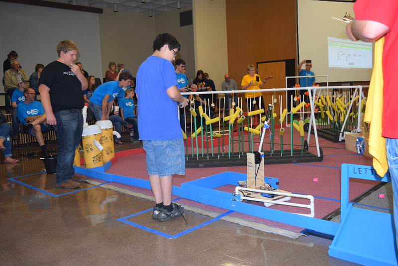 A Holyoke Junior and Senior High School team member guides the team's robot out of the corral, as another team member watches to give tips, during the Golden Plains BEST Robotics Challenge Saturday, Oct. 29, 2016.
