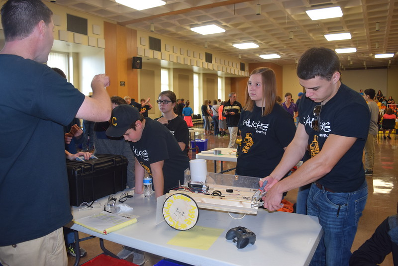 Caliche Junior and Senior High School team members listen as coach David Monheiser gives them some tips while they make adjustments to their robot during a break between matches at the Golden Plains BEST Robotics Challenge Saturday, Oct. 29, 2016.