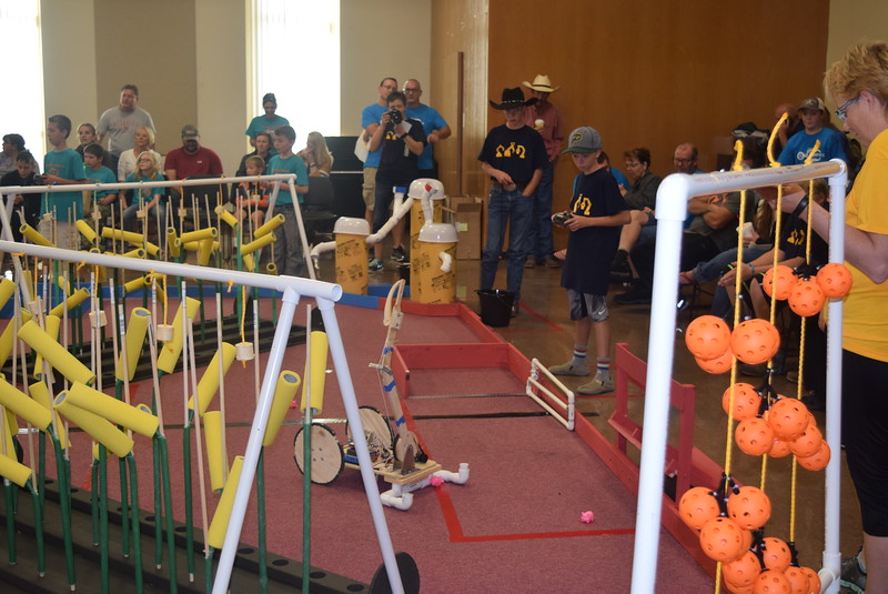 "Peetz Cybermen team members work to corral pigs with their robot during the Golden Plains BEST Robotics Challenge Saturday, Oct. 29, 2016. The theme was ""Bet the Farm."" Students had to create a robot that would be able to plant corn seeds, harvest and deliver corn, harvest and deliver tomatoes and lettuce, corral and secure loose pigs and feed them, and turn on a water valve."